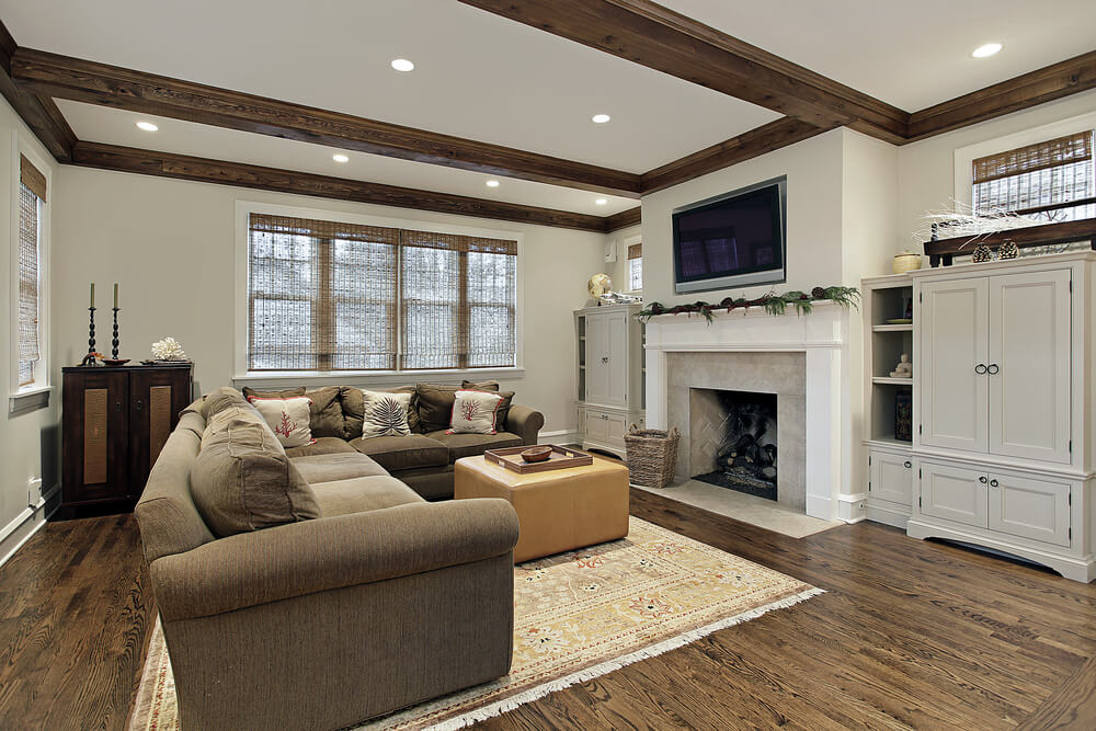 burning fireplace  Plain white walls and all wood ceiling with beams