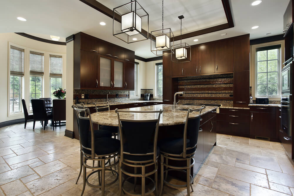 The darkness of these cabinets takes them into the background, as this kitchen allows the unusual round breakfast bar and modern light fixtures to take center stage.