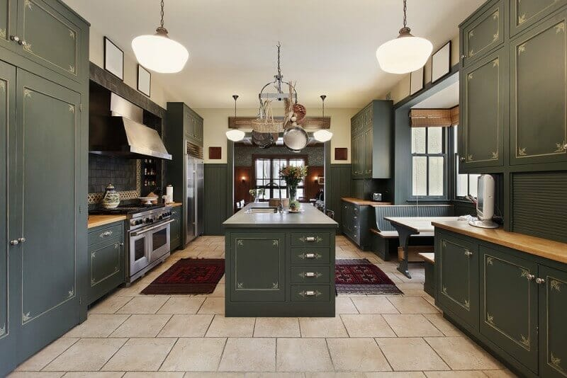 Stepping away from the usual brown and black cabinets used to achieve dark kitchens, this kitchen uses a dark olive green and grey to achieve the striking but alternative kitchen color scheme.