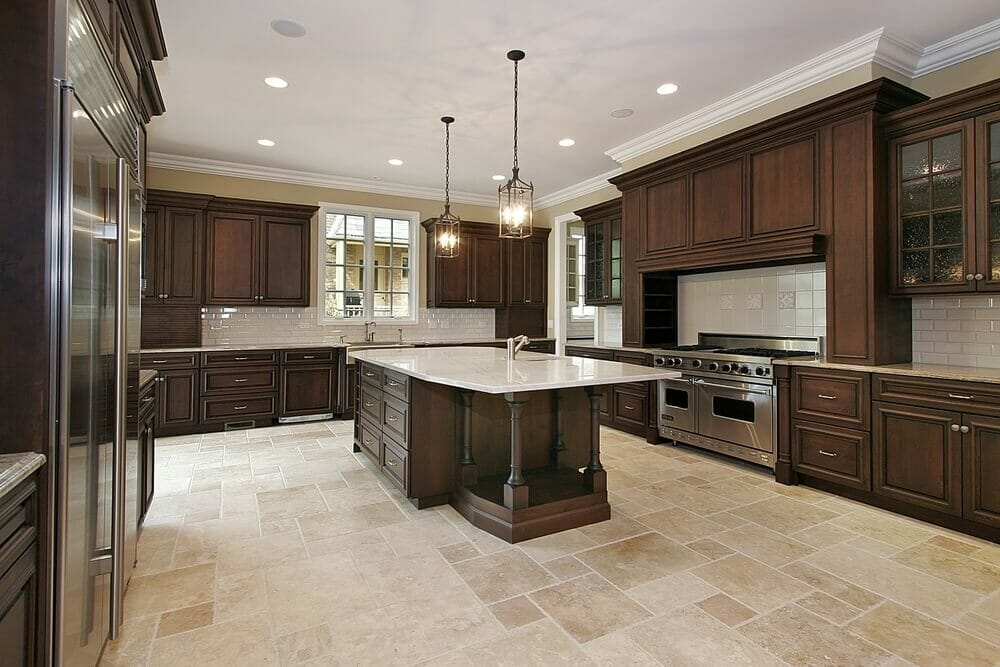 modern appliances meet gothic style light fittings and traditional wooden cabinets in this kitchen to create