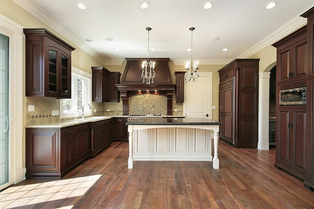 It's easier to use dark colors in larger rooms because they can shrink smaller rooms. This large kitchen is a wonderful example of how ornate and dark colored wooden cabinets can bring luxury and pure elegance to the home.