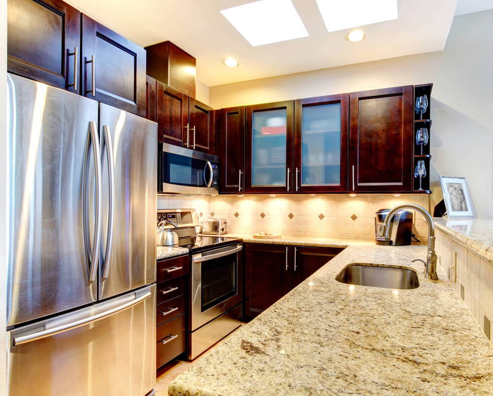 under cabinet lighting and a very reflective and large refrigerator is a very clever design trick - Kitchen Designs Dark Cabinets
