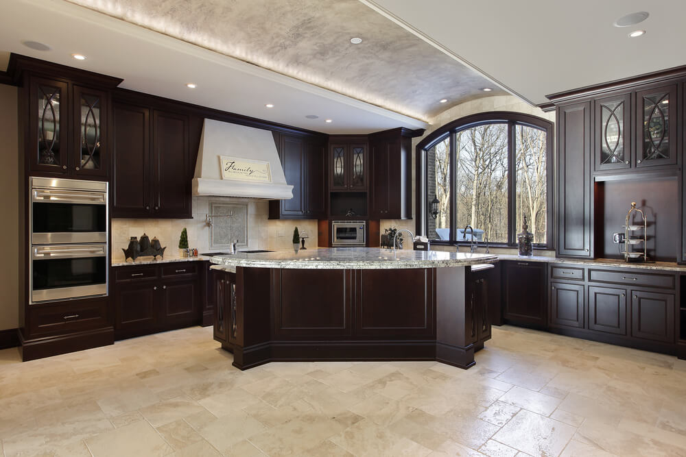 There is plenty of floor, wall, and ceiling space in this huge kitchen to add plenty of lightening and complementing cream to balance out these striking dark wooden cabinets.