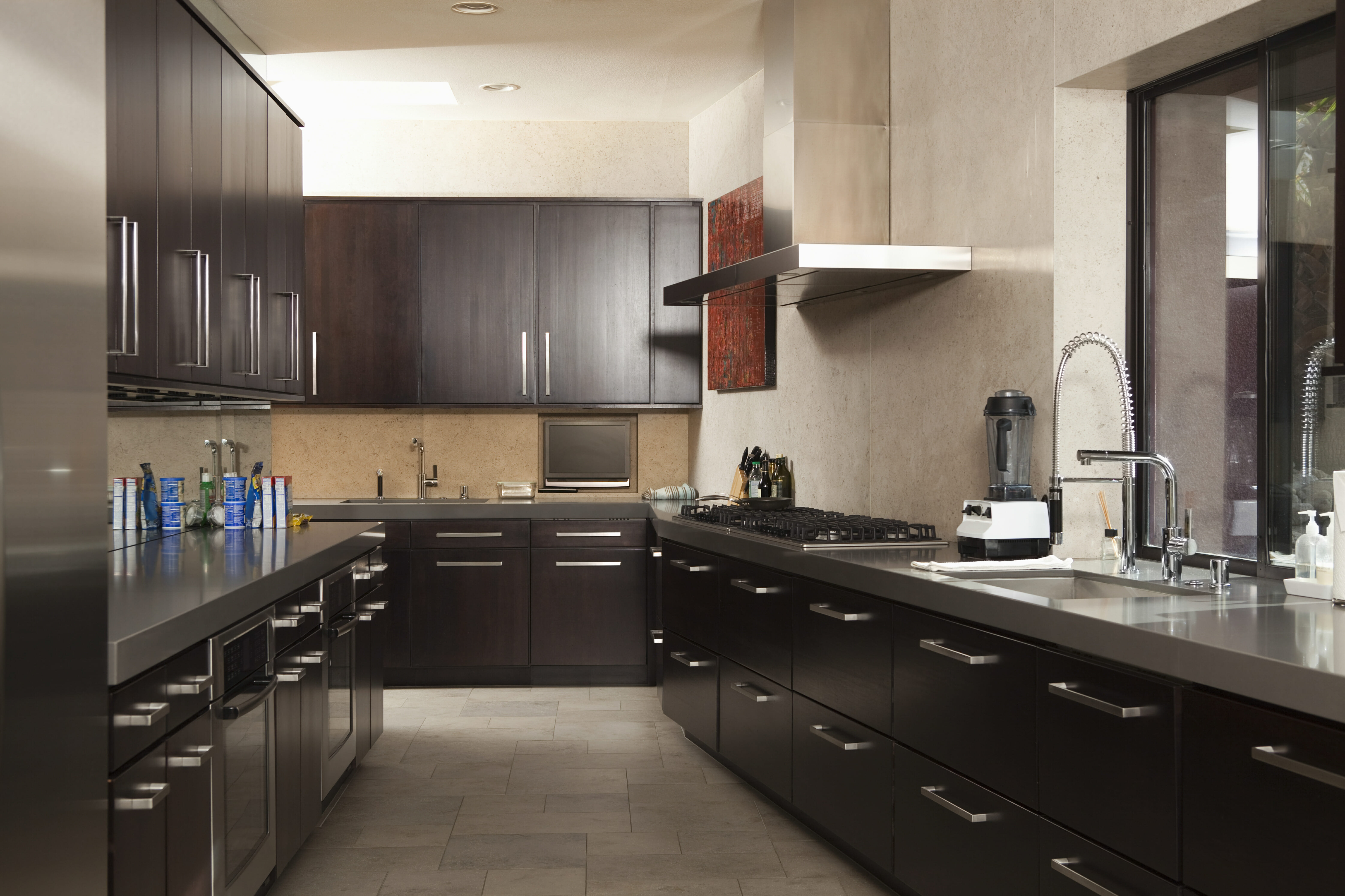 Semi-matte cabinets like these provide some light reflection, but a lighter floor, walls, and metallic workspaces prevent the room from feeling too dark, but still use a sleek black color as the room's biggest feature.