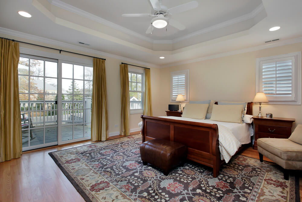 Master bedroom with tray ceiling and deck view
