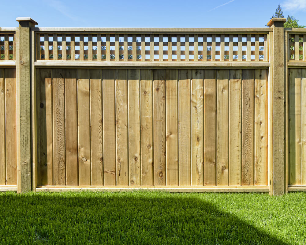 We love beautiful cedar fence designs. This one mixed with panels and lattice work is subtle yet will dress up any home.