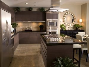 The tan and brown tiles on the floor in this kitchen match the ones on the wall, creating a cohesive look that goes well with the muted browns of the cabinet. This is definitely an understated, but still sleek look.