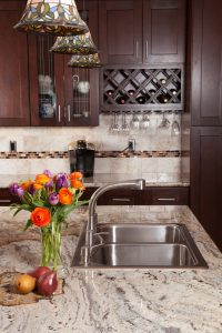 A light granite slab with a little bit of dark color accents goes well with the granite tiles on the walls behind. With the glass it breaks up the monotony of color but also highlights what's already in the look.