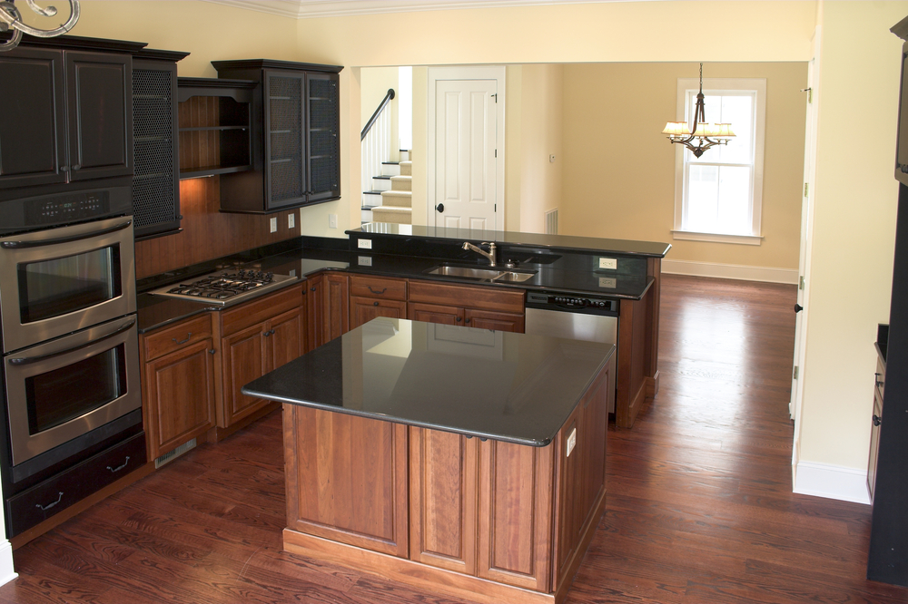 Here you're getting a little bit of a mix with the black granite countertops paired with black cupboards as well as deeper cherry. It definitely gives your kitchen a more rustic and masculine feel.