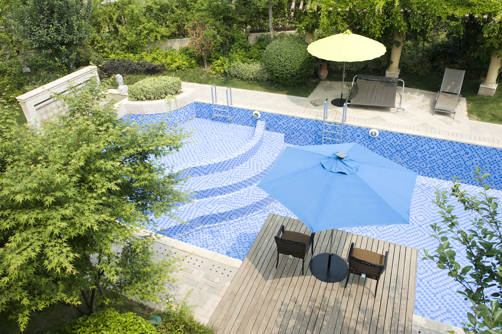 This pool has a little bit of space directly around it with a couple patios for relaxation but it also has a decent amount of greenery too. You'll be able to enjoy the green space while you relax in the pool.